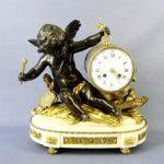 """Кабинетные часы """"Амур, бьющий в барабан"""". Бронза, патинирование, золочение, мрамор. Франция, Париж, XIX век. Высота: 36 см. Длина подиума: 34 см; ширина подиума: 17 см."""