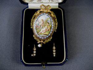 Комплект: брошь-подвеска, серьги. Эмаль, ручная роспись, жемчуг. Золото 585; брошь: 15,2 г (длина: 6,0 см); серьги: 1,1 г. Франция, конец XVIII века. Оригинальный футляр.
